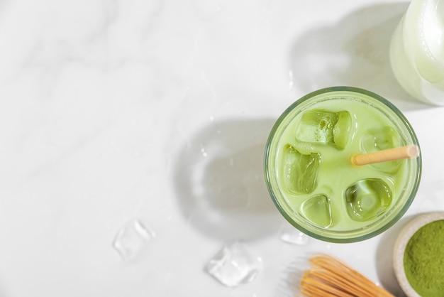Iced green matcha latte in einem glas auf weißer oberfläche mit harten schatten