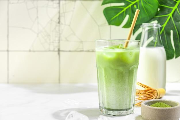 Iced green matcha latte in einem glas mit milchflasche auf weißer fliesenoberfläche mit harten schatten und monstera-blättern