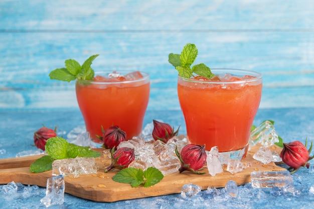Iced roselle teeglas mit frischen rosellefrüchten auf holztisch für ein gesundes kräutergetränkkonzept. kräuter-bio-tee für gute gesundheit.