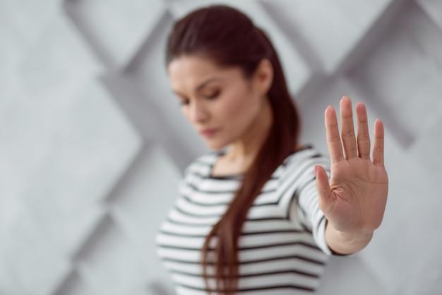 Ich bin allein. der selektive fokus einer weiblichen hand, die ihnen gezeigt wird, ist eine nette schöne verärgerte frau