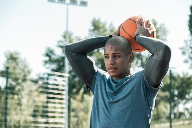 Ich bin bereit. angenehmer junger mann, der einen ball über sich hält, während er sich darauf vorbereitet, ihn zu werfen
