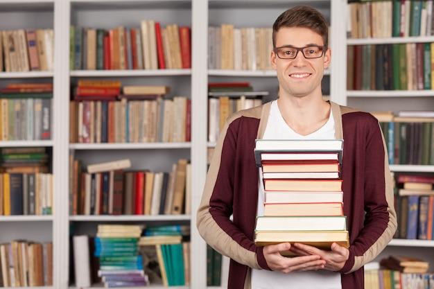 Ich bin bereit für meine abschlussprüfung. fröhlicher junger mann, der einen bücherstapel hält und lächelt, während er in der bibliothek steht