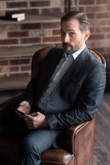Ich bin der boss. hübscher ernsthafter selbstbewusster mann, der einen anzug trägt und ein handy hält, während er im sessel sitzt