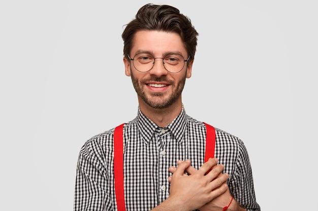 Ich bin dir so dankbar! attraktiver, freundlich aussehender hipster mit trendigem haarschnitt, der beide handflächen im herzen hält