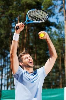 Ich bin ein sieger! glücklicher junger mann im poloshirt, der seinen tennisschläger hochhebt, während er auf dem tennisplatz steht