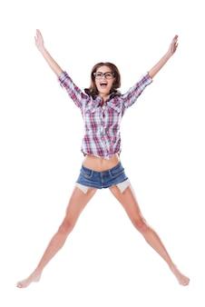 Ich bin ein star! volle länge der attraktiven jungen frau mit brille und funky kleidung, die springen und lächelt, während sie auf weißem hintergrund isoliert ist