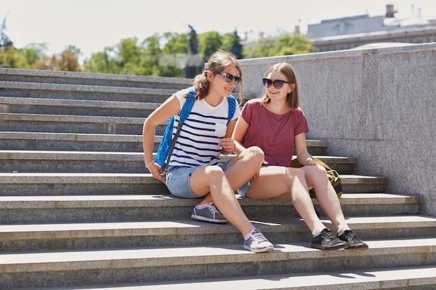 Ich bin froh, dass die besten freundinnen sonnenbrillen, shorts und turnschuhe tragen, einen rucksack tragen, auf treppen sitzen und von der universität zurückkehren