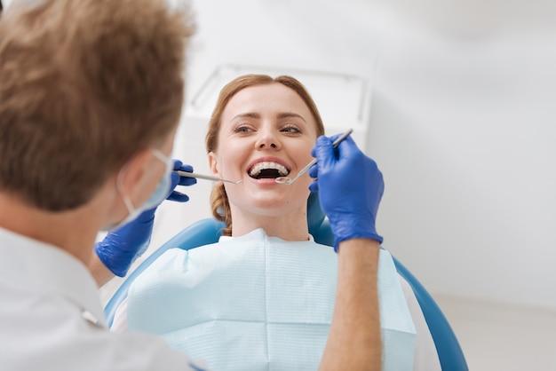 Ich bin froh, dass die hübsche dame eine gute nachricht von ihrem zahnarzt hört, nachdem er ihre zähne untersucht und gesagt hat, sie sei gesund