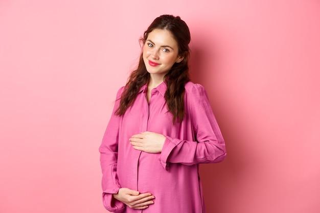 Ich bin gestopft. erfreutes lächelndes mädchen, das ihren bauch zeigt, nachdem es gut gegessen hat und bauch mit zufriedenem gesicht reibt. junge schwangere frau, die kind erwartet, art betrachtet kamera, rosa wand.