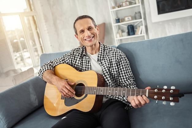Ich bin glücklich. hübscher fröhlicher gut gebauter mann, der lächelt und gitarre spielt, während er auf der couch sitzt