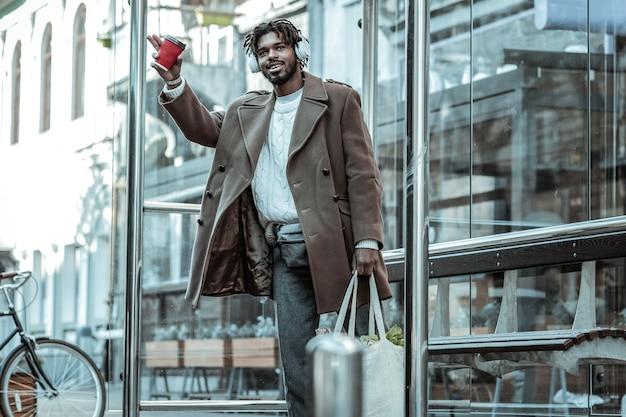Ich bin hier. erfreulicher mann, der lächeln auf seinem gesicht hält, während einkaufstasche mit produkten hält