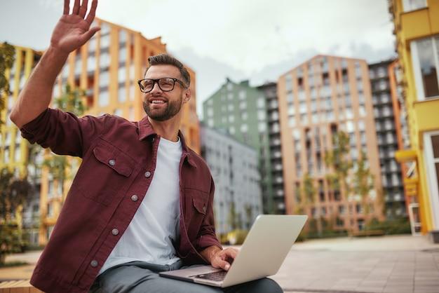 Ich bin hier junger und fröhlicher, gutaussehender mann mit stoppeln in freizeitkleidung und brille winkt einem freund zu, während er mit laptop im freien auf der bank sitzt. gruß. bloggen. stadt leben