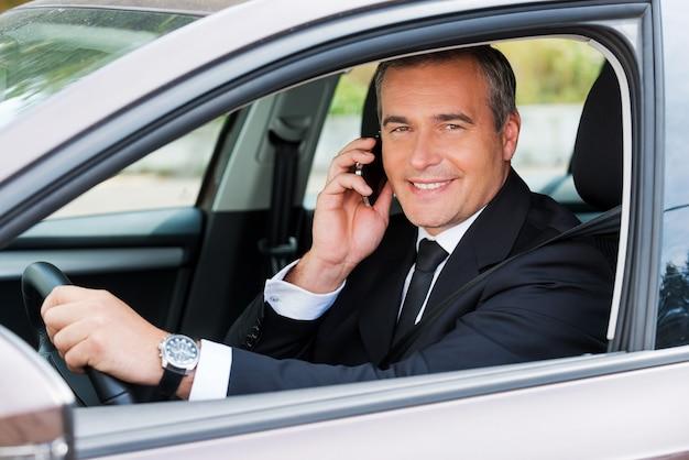 Ich bin in einer minute da! fröhlicher reifer mann in formeller kleidung, der auto fährt und mit dem handy spricht