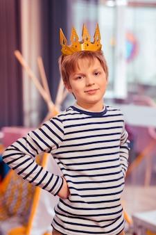 Ich bin könig. charmanter blonder junge, der positivität ausdrückt und aufwirft
