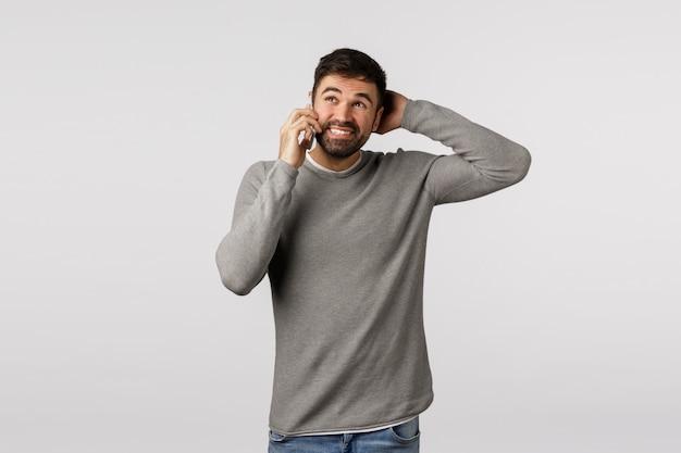 Ich bin mir nicht sicher. ahnungsloser, unentschlossener junger mann, der versucht, verantwortung zu vermeiden, die arbeit auszulassen, ausreden zu machen, den kopf als sprechendes telefon zu kratzen, nachdenklich wegzuschauen, verwirrt zu stehen, das smartphone in die nähe des ohrs zu halten