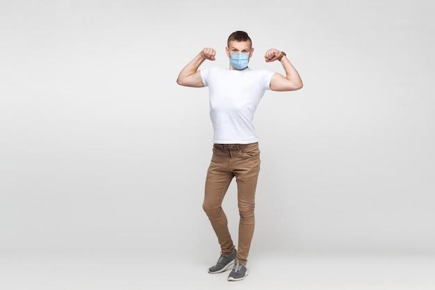 Ich bin stark. ganzaufnahme des jungen mannes im weißen hemd mit chirurgischer medizinischer maske, die steht und seinen bizeps zeigt und mit hochmütigem gesicht schaut. innenstudio erschossen, auf grauem hintergrund isoliert.