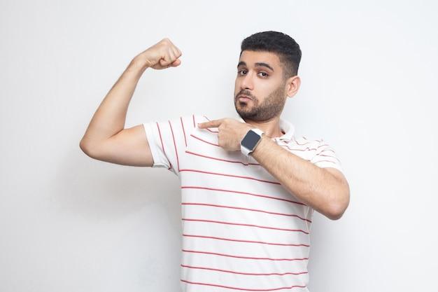 Ich bin stark. porträt eines stolzen, gutaussehenden, bärtigen jungen mannes in gestreiftem t-shirt, der auf seinen bizeps zeigt und mit zufriedenem gesicht in die kamera schaut. indoor-studioaufnahme, isoliert auf weißem hintergrund