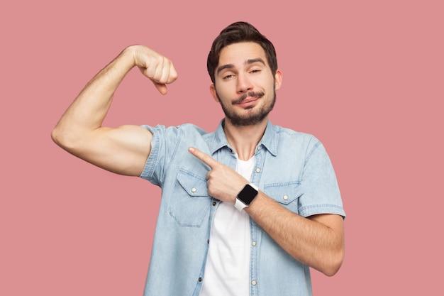 Ich bin stark und ich kann alles. porträt eines stolzen, gutaussehenden, bärtigen jungen mannes im blauen freizeithemd, das zeigt und seinen starken bizeps zeigt. indoor-studioaufnahme, isoliert auf rosa hintergrund.