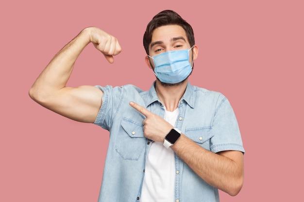 Ich bin stark und ich kann alles. porträt eines stolzen jungen mannes mit chirurgischer medizinischer maske im blauen hemd, das zeigt und seinen starken bizeps zeigt. indoor-studioaufnahme, isoliert auf rosa hintergrund.