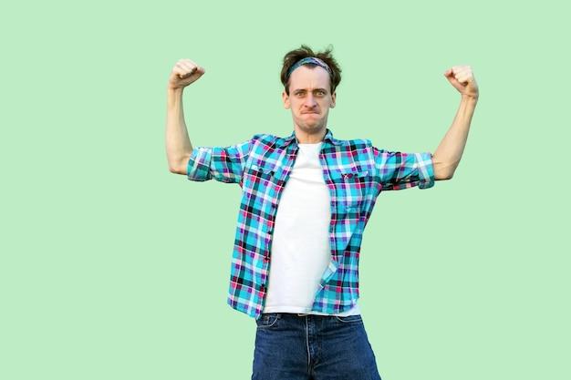 Ich bin stark und unabhängig. porträt eines lustigen jungen mannes in lässigem blau kariertem hemd, stirnband mit starker geste und blick in die kamera. indoor-studioaufnahme, auf grünem hintergrund isoliert.