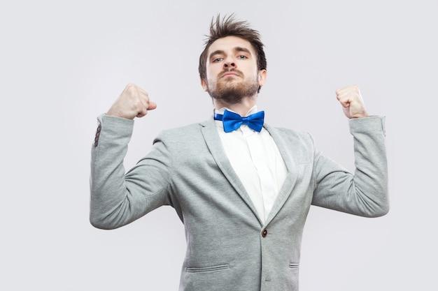 Ich bin stark und unabhängig. porträt eines zufriedenen, stolzen, gutaussehenden bärtigen mannes in lässigem grauem anzug und blauer fliege, der die kamera steht und betrachtet. indoor-studioaufnahme, isoliert auf hellgrauem hintergrund