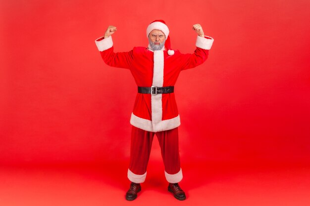Ich bin stark! weihnachtsmann demonstriert macht in seinen händen und zeigt bizeps.