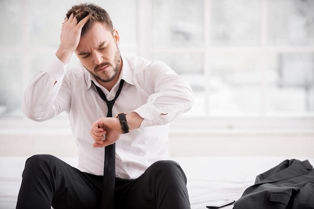 Ich bin wieder zu spät! frustrierter junger mann in hemd und krawatte, der die zeit überprüft und die hand im haar hält, während er auf dem bett sitzt