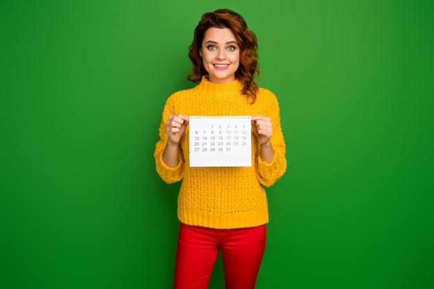 Ich bin ziemlich frei! foto der hübschen fröhlichen dame halten papierkalender, der monat ohne pläne zeigt, tragen gelbe strickpullover rote hosen isolierte grüne farbwand