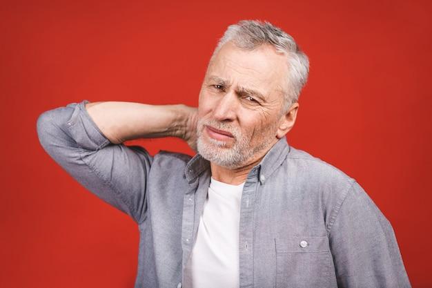 Ich brauche eine massage. frustrierter älterer mann in der freizeitkleidung, die im stehen hand auf seinem hals hält.