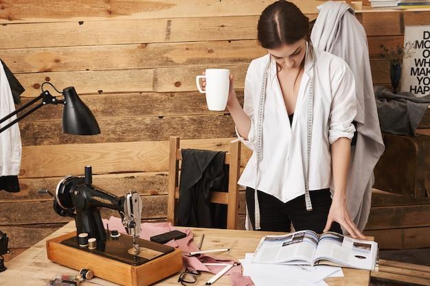 Ich brauche inspiration. porträt des niedlichen weiblichen schneiderlesemagazins, während tee trinkend und pause in der werkstatt, mit nähmaschine unter neuem kleidungsstück arbeitend