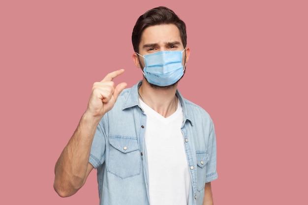 Ich brauche noch ein paar. porträt eines jungen mannes mit chirurgischer medizinischer maske im blauen hemd im casual-stil, der in die kamera schaut und um etwas bettelt. indoor-studioaufnahme, isoliert auf rosa hintergrund