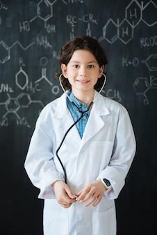 Ich denke an meine zukünftige karriere. intelligenter lächelnder fröhlicher junge, der nahe der tafel in der schule steht, während er medizinische lektion hat und stethoskop verwendet