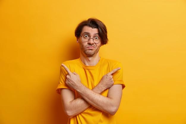 Ich frage mich, was ich wählen soll. der zögerliche hipster-typ kreuzt die hände über die brustpunkte in verschiedene richtungen, gekleidet in einem lässigen t-shirt, das über einer gelben wand isoliert ist und nicht weiß, wie oder welche entscheidung am besten ist