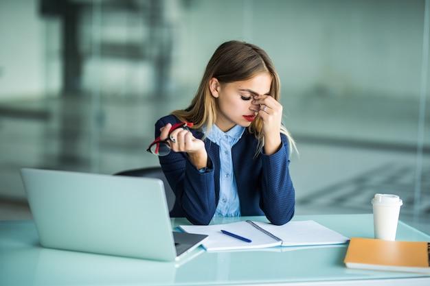 Ich fühle mich müde und gestresst. frustrierte junge frau, die augen geschlossen hält und nase massiert, während sie an ihrem arbeitsplatz im büro sitzt
