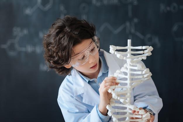 Ich genieße meine wissenschaftliche forschung. intelligenter neugieriger aufmerksamer junge, der in der schule vor der tafel steht, während er das chemieprojekt studiert und arbeitet