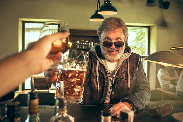 Ich genieße meinen lieblingsbrot und mein lieblingsbier. mann mit bierkrug, der am tisch sitzt.