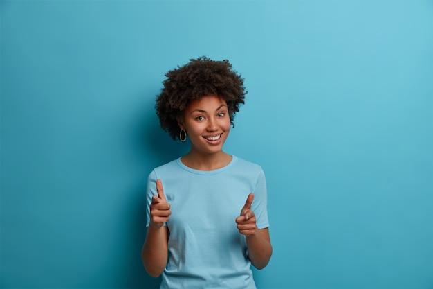 Ich glaube an sie. positive dunkelhäutige freundin macht eine fingerpistolengeste, ermutigt jemanden, wählt das team aus, lobt für gute arbeit, lächelt breit, trägt ein lässiges blaues t-shirt und steht drinnen