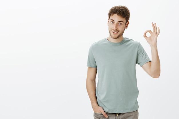 Ich habe alles unter kontrolle. porträt des positiven gutaussehenden mannes im lässigen outfit, hand hebend mit okay oder ok geste
