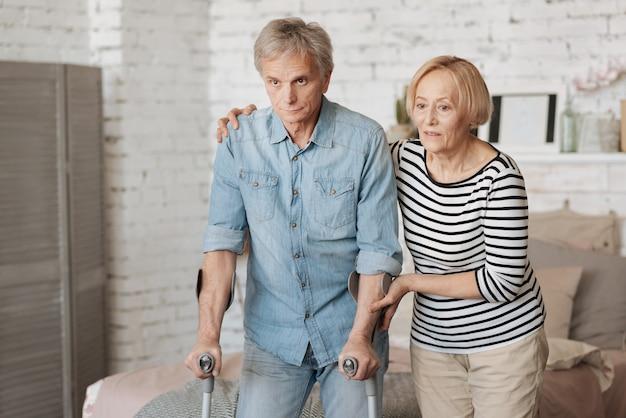 Ich habe deinen rücken. produktiver, motivierter, gealterter gentleman, der einen spaziergang machen und dafür die krücken benutzen möchte, während seine frau ihn unterstützt