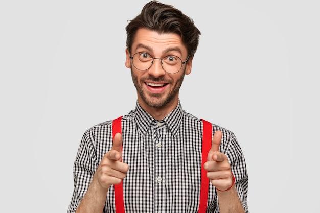 Ich habe dich ausgewählt! der lächelnde positive junge männliche geschäftsmann zeigt direkt mit beiden zeigefingern, drückt seine wahl aus, hat einen glücklichen ausdruck, trägt ein kariertes hemd und rote hosenträger