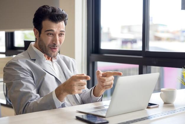 Ich habe die herausforderung beendet ein sehr glücklicher geschäftsmann benutzt einen laptop im büro