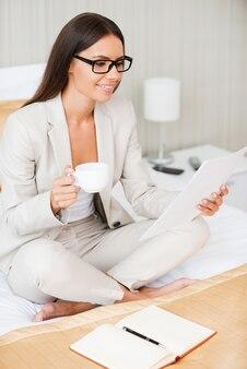 Ich habe diesen vertrag! schöne junge lächelnde geschäftsfrau im anzug, die kaffee trinkt und ein dokument hält, während sie auf dem bett im hotelzimmer sitzt
