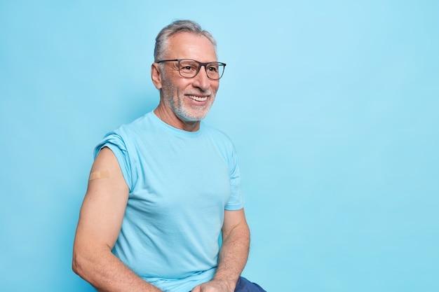 Ich habe eine covid-19-impfung bekommen. lächelnder bärtiger älterer mann zeigt nach der impfung schulter mit pflaster