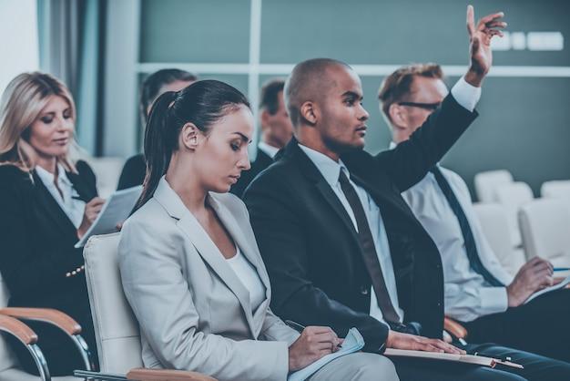 Ich habe eine frage! gruppe von geschäftsleuten in formeller kleidung, die auf den stühlen im konferenzsaal sitzen und etwas in ihre notizblöcke schreiben, während der gutaussehende afrikanische mann seinen arm hebt