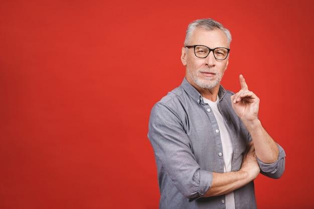 Ich habe eine großartige idee! porträt eines reifen ernsten geschäftsmannes, der brillen trägt, die gegen roten hintergrund lokalisiert werden.
