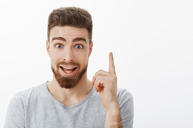 Ich habe eine idee. enthusiastischer und aufgeregter glücklicher kreativer kaukasischer kerl mit bart und niedlichen blauen augen, die zeigefinger in der eureka-geste anheben, die mit chef spricht, der perfekten plan über graue wand präsentiert