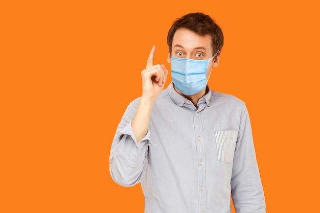 Ich habe eine idee. porträt eines aufgeregten jungen arbeitermannes mit chirurgischer medizinischer maske, der mit überraschtem gesicht steht und eine idee hat. indoor-studioaufnahme auf orangem hintergrund isoliert.