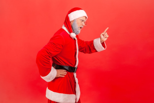 Ich habe es dir gesagt! seitenansicht eines älteren mannes mit grauem bart, der ein weihnachtsmann-kostüm trägt und mit aufmerksamkeitszeichen steht, mit fingerwarngeste. innenstudio erschossen auf rotem hintergrund isoliert.