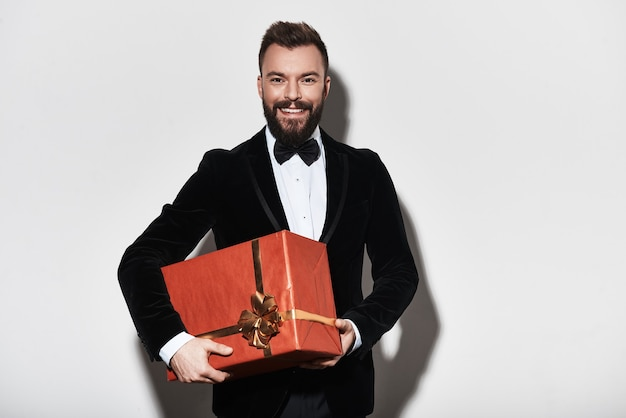 Ich habe etwas für dich. hübscher junger mann im vollen anzug, der eine geschenkbox trägt und lächelt, während er vor grauem hintergrund steht