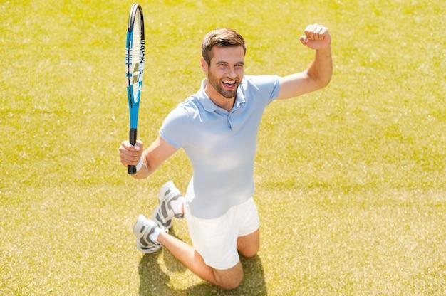Ich habe gewonnen! draufsicht eines glücklichen jungen mannes im polohemd, der tennisschläger hält und gestikuliert, während er auf dem tennisplatz kniet